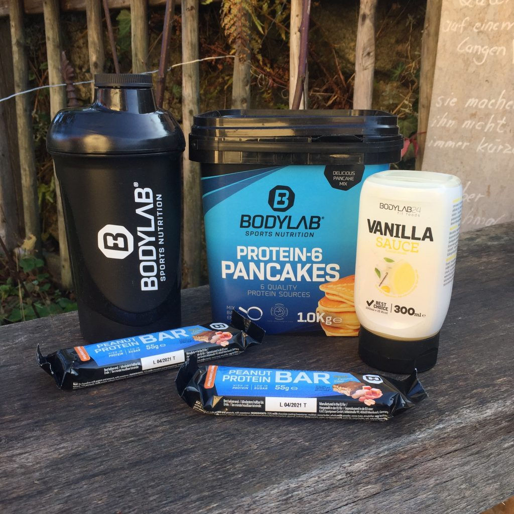 Bodylab24 Protein Pancakes, Protein Riegel und Eiweißshaker in einem Garten